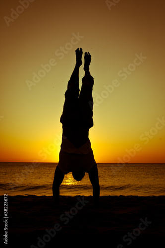 Silhouette of a man standing on his hands on the beach at sunset