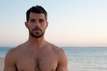 Handsome muscular man on the beach.