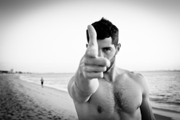 Muscular man on the beach pointing at camera. Black and white