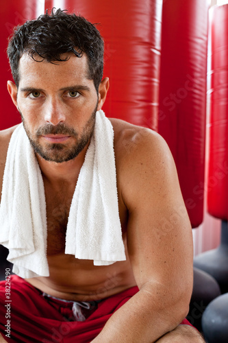 Handsome muscular man sweating with towel on his shoulders