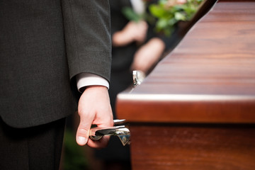 coffin bearer carrying casket at funeral