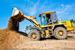 Wheel loader machine unloading soil during earthmoving works