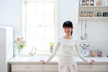 attractive asian woman relaxing in kitchen