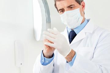 Arzt zieht sich Handschuhe an