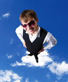 Young businessman against cloudy sky background