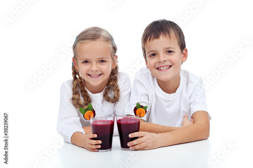 Happy kids with fresh red vegetables juice