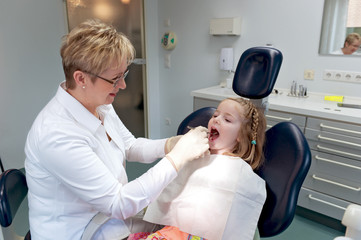 Zahnärztin untersuchet Kind