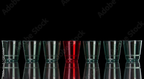 Straight row of colored plastic glasses on black with reflection
