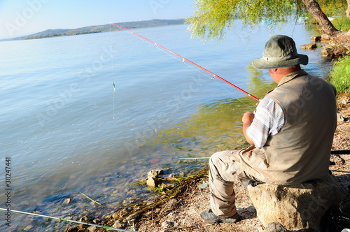 fisherman is angling, sitting by lake