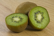 Close-up of 2 Kiwis with One Cut in Half on a Cutting Board