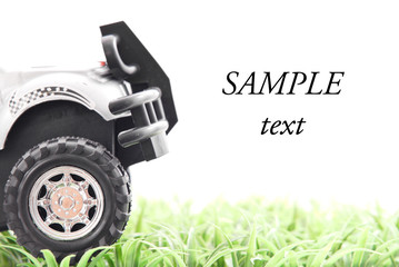 Toy Truck Driving on Grass with Space for Text