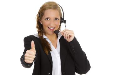 Sympathische Frau mit Headset zeigt Daumen hoch