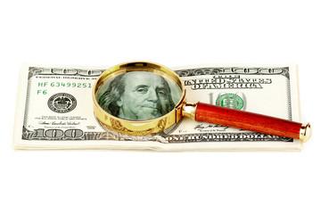 Hundred dollar bill under a magnifying glass