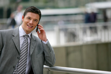 Businessman making phone call whilst leaning against railing
