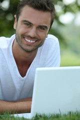 Smiling man outdoors with a laptop