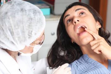 Patientin zeigt Zahnarzt wo es schmerzt