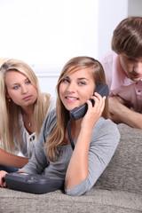 Three teenagers making a telephone call