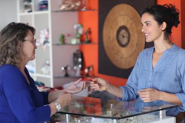 Ältere Dame bezahlt im Laden mit Kreditkarte