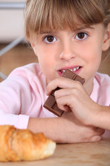 Little girl eating chocolate bar for breakfast
