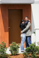 Couple embracing at their front door