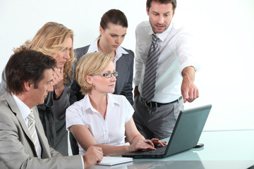 Business team sitting around a laptop computer