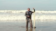Happy businessman with surfing board standing in the sea