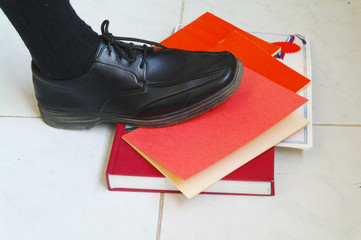 Foot in a boot stepping on red legal books and documents