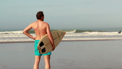 Man with surfing board standing by the sea, slow motion