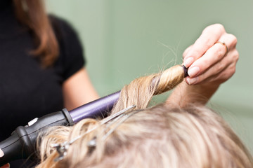 Hairdresser to curl the hair in a beauty salon
