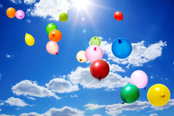 Color flying balloons in blue sky with clouds and sun