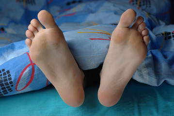Girl feet put out from the blanket
