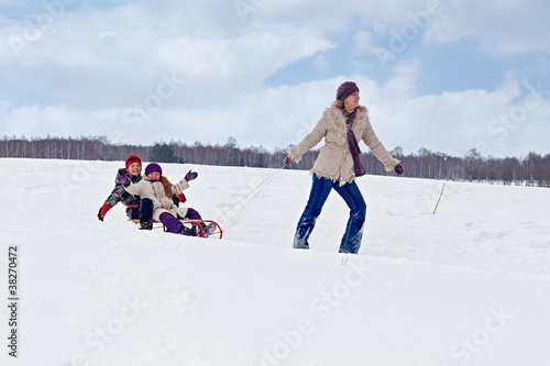 Children sleigh riding - their mother helping