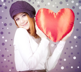 Beautiful red-haired girl in cap with toy heart.