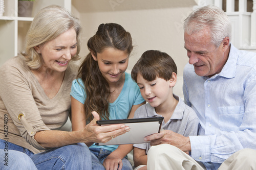 Seniors & Children Grandparents & Grandchildren Using Tablet Com