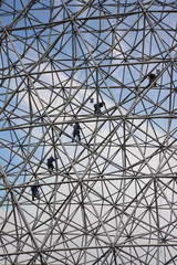 Climbers on a metallic net structure painting the sky.