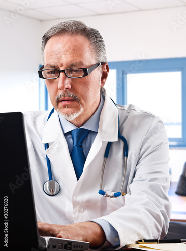 Portrait of a doctor using his laptop