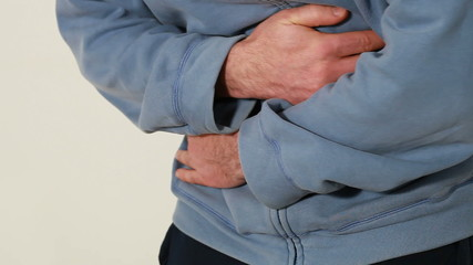 Man holding his hands over his aching stomach