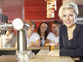 Smiling young woman drinking a glass of beer in a pub
