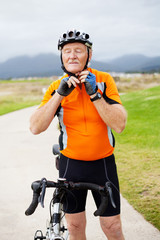 senior man putting his cycling helmet on
