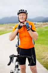 senior man putting his cycling helmet on
