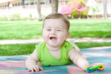 Smiling baby lying and played in the park
