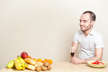 Portrait of a young man having a glass of wine while cooking. co