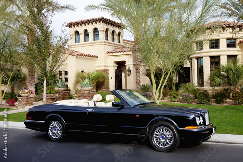 Luxurious convertible car parked in front of a mansion house