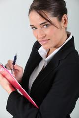 Brunette holding clipboard and pen