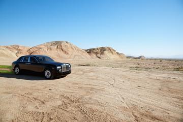 Black eco-friendly Rolls Royce car running off-road on unpaved road
