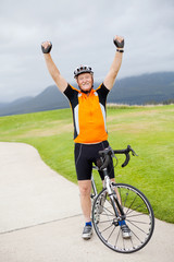 cheerful active senior man on bicycle with arms up