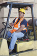 Forklift driver driving in warehouse