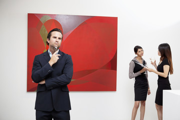 Young man thinking with two women talking in background in museum
