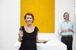 Cheerful woman standing in front of yellow painting with man in background