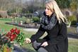 Frau legt Blumen auf Grab
